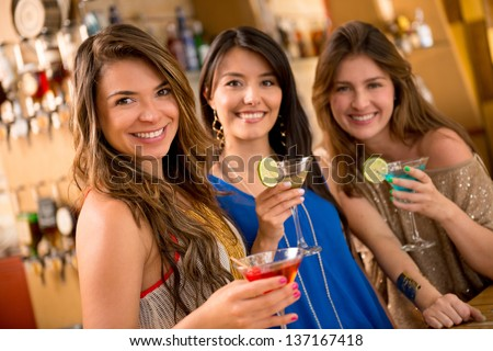 Beautiful group of girls having drinks at the bar and smiling