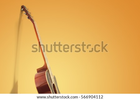 Beautiful guitar leaning on yellow wall