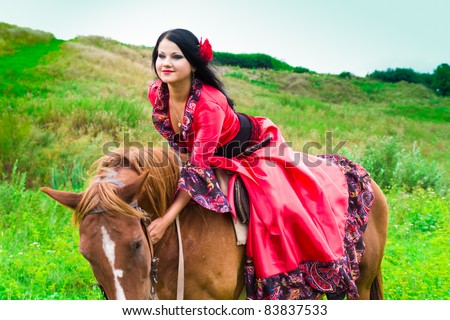 stock photo : Beautiful gypsy girl riding a horse in the field