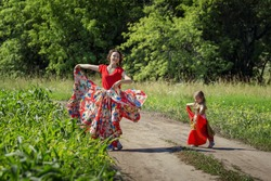 Beautiful gypsy woman dancing in a blooming field in a bright red dress