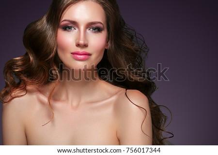 Shutterstock Beautiful hair woman beauty skin portrait over dark background. Long beautiful healthy hair model girl stock image. Studio shot.