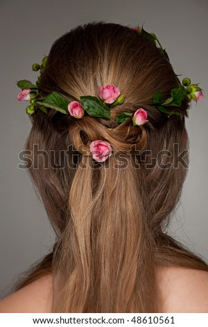 beautiful hairdo with small pink roses over grey background
