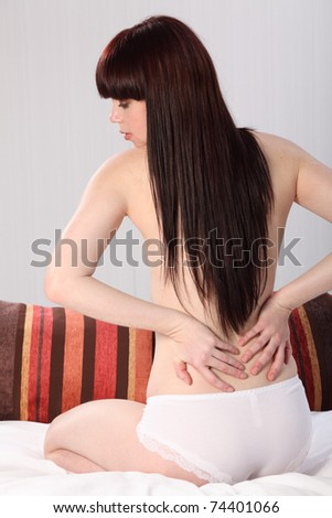 Beautiful half naked young woman sitting in bed, checking for muscle pain in her lower back with both hands.