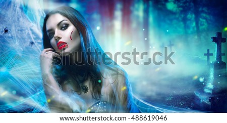 Beautiful Halloween Vampire Woman portrait. Beauty Sexy Vampire Witch lady with blood on mouth posing in cemetery, wearing spider web. Fashion Art design. Mysterious Model girl with Halloween make up