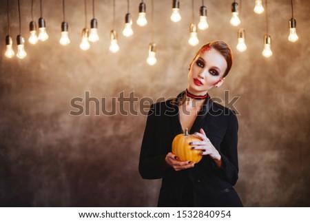 Beautiful Halloween Vampire Woman portrait. Mysterious Model girl with Halloween make up
