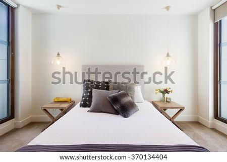Beautiful hamptons style bedroom decor in luxury home interior with pendant lighting