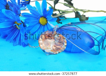 Beautiful hand cut and fired  heart  glass pendant  with fantastic blue flowers are on the bright blue napkin background.  (It's nice present idea).