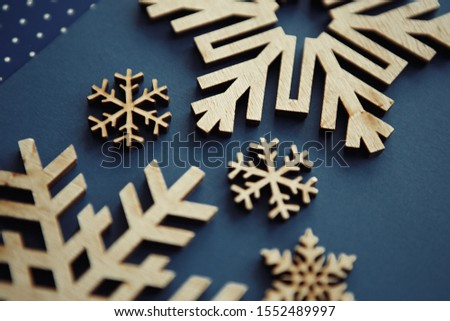 Photo of Beautiful hand made snow flakes for Happy New Year and Christmas Eve celebration.Hand crafted wooden rustic snowflake figures on blue background.Edited with fading film colors,shot from above