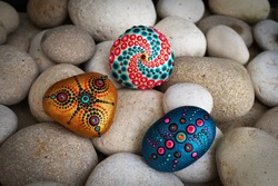 Beautiful hand painted mandala stones lies on the rocks