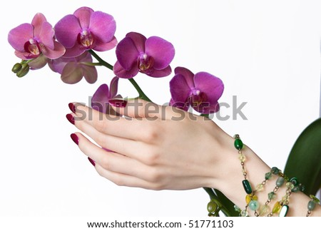 Beautiful hand with pink manicure, green beads touching orchid