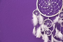 Beautiful handmade dream catcher on purple wall, closeup. Space for text