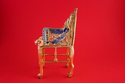 beautiful handmade duplicate of King Pharaoh Tutankhamun throne on red background - travel to Egypt  concept.