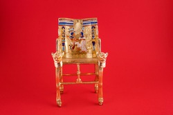 beautiful handmade duplicate of King Pharaoh Tutankhamun throne on red background - travel to Egypt  concept.