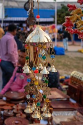 Beautiful handmade Rajasthani multicolour wind chimes is displayed in a shop for sale in blurred background. Indian handicraft (selective focus)