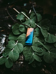 Beautiful handmaded necklace (amulet) with shining blue epoxy with green leafs on background - moody folk style photo. Handmade product of wood on wooden backround in dark forest.