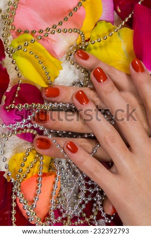 Beautiful hands with a nice manicure. Gel nails are covered with red polish. Spa treatment for hands. Spa treatment, bath for hands. Hands on a background of rose petals in spa salon.