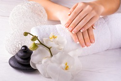 Beautiful hands with manicure and orchid flower