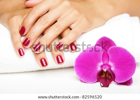 Beautiful hands with manicure and purple orchid flowers