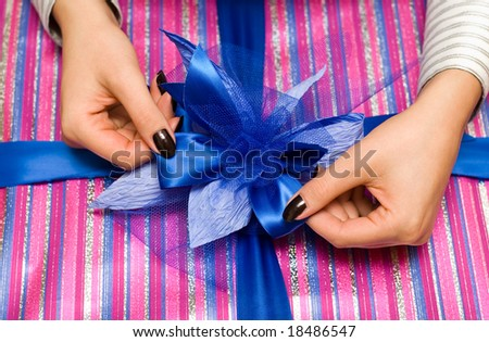 Beautiful hands wrapping giftbox