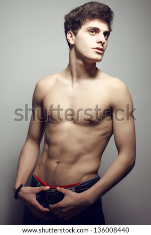 Beautiful (handsome) muscular male model with nice abs in jeans posing over gray background. Perfect skin and body. Fashion studio portrait.