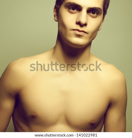Beautiful (handsome) muscular male model with nice body and lovely tan posing over light-gray background. Close up. Emotive studio portrait.