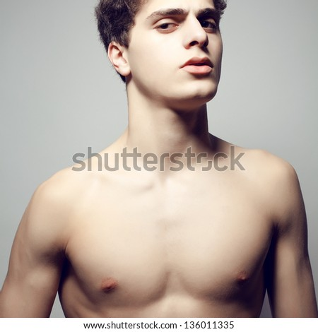 Beautiful (handsome) muscular male model with nice body posing over light-gray background. Close up. Emotive studio portrait.