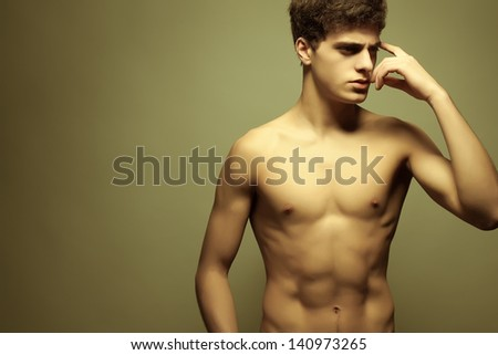 Beautiful (handsome) muscular male model with nice body posing over light-yellow background. Copy-space. Studio shot. - stock photo