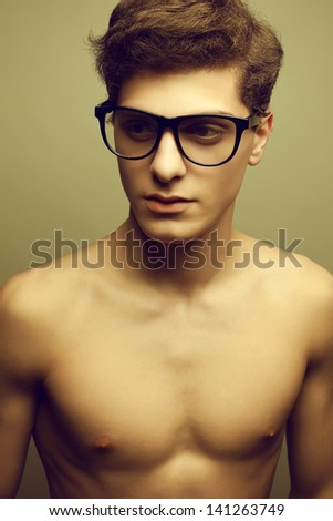 Beautiful (handsome) muscular male model with nice body wearing trendy glasses and posing over light-gray background. Hipster and vintage (retro) style. Close up. Studio portrait.