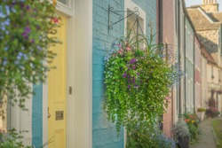 Beautiful Hanging Flower Baskets Hang Outside Colorful Painted Houses on a Street in Scotland