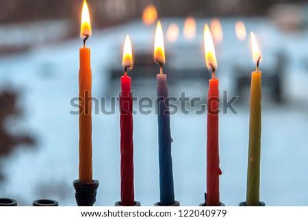 Beautiful Hanukkah menorah chanukkiah with glowing candles in a window