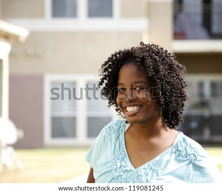 Beautiful happy African-American girl in front of modern apartment (condo) building