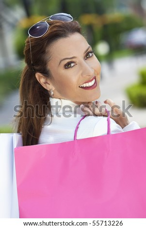 Beautiful, happy and fashionable woman with colorful pink and white shopping bags