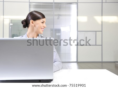 Beautiful happy and smiling business woman working on computer at her office and looking right from the camera