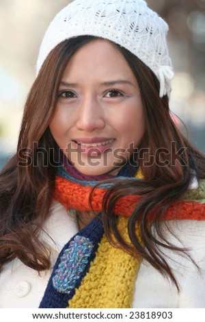 Beautiful happy Asian Woman in White hat and Colorful Knit Scarf Laughing, close up portrait suitable for a variety of seasonal, winter themes