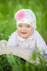 Beautiful happy baby girl sitting on green grass in the park. Children and infancy concept.