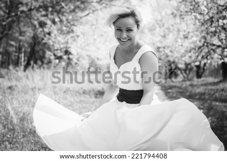 Beautiful happy blonde woman in the park on a warm summer day.Portrait of young lovely woman in spring flowers.Beautiful spring girl in blooming tree.Beautiful woman with white flowering tree