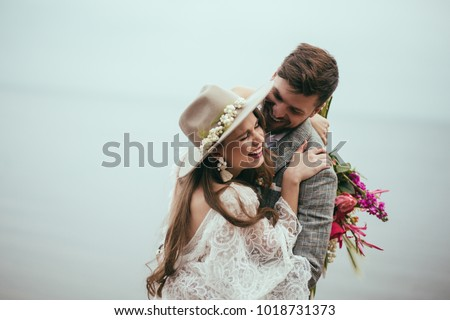 beautiful happy bride and groom in boho style laughing at lake #1018731373