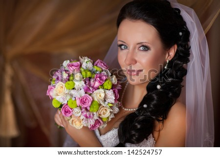 Beautiful Happy bride with wedding flowers bouquet in white dress with wedding hairstyle and makeup. Smiling woman in wedding dress waiting for groom. Pretty brunette girl bride. Jewelry and Beauty