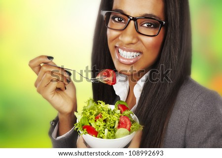 beautiful happy businesswoman eating salad over green background