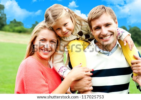 Beautiful happy caucasian family of three. Father, mother and daughter - stock photo