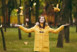 Beautiful happy caucasian young smiling brown-hair woman in yellow coat, jeans, boots in green forest. Fashion female model throwing up fall leaves standing and walking in early autumn park outdoors