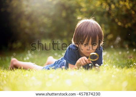Beautiful happy child, boy, exploring nature with magnifying glass, summertime Stock photo ©
