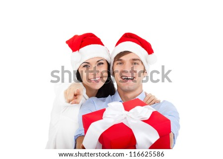 beautiful happy christmas holiday couple love smiling embracing in red new year hat cap, man and woman hold gift box present smile point finger at you looking at camera, isolated over white background