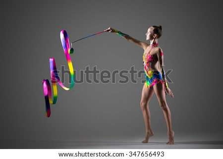 Beautiful happy cool young fit gymnast athlete woman in colorful sportswear working out, doing rhythmic gymnastics exercise Spirals with art ribbon, dancing, full length, studio, dark background