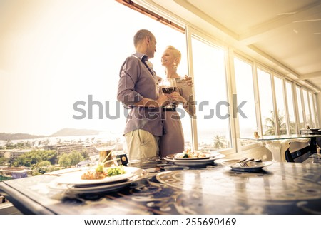 Beautiful happy couple having romantic dinner at sunset in a luxury restaurant Woman and her husband celebrating wedding anniversary