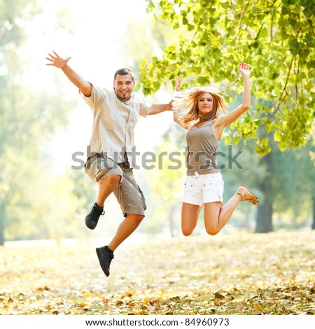 Beautiful happy couple jumping in the park #84960973