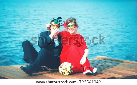 Beautiful happy couple of lovers in masquerade masks - a man in a suit and a woman in a red dress sitting on a pier against a ripple of turquoise water. Vintage toned filter, selective focus.