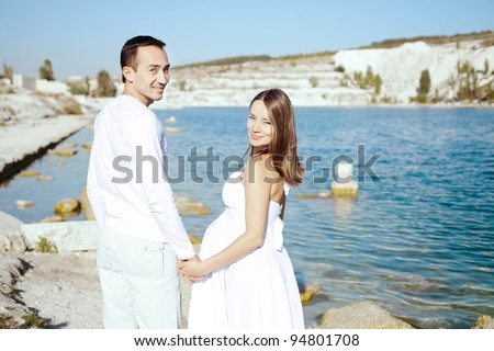 beautiful happy couple standing arm in arm on the lake. A young wife is pregnant