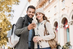 Beautiful happy couple using smartphone. Young joyful smiling woman and man looking at mobile phone in a city in autumn.  Technology, travel, tourism, students concept