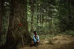 beautiful happy cute stylish girl sitting near a big tree in the mountains on a background of a forest
